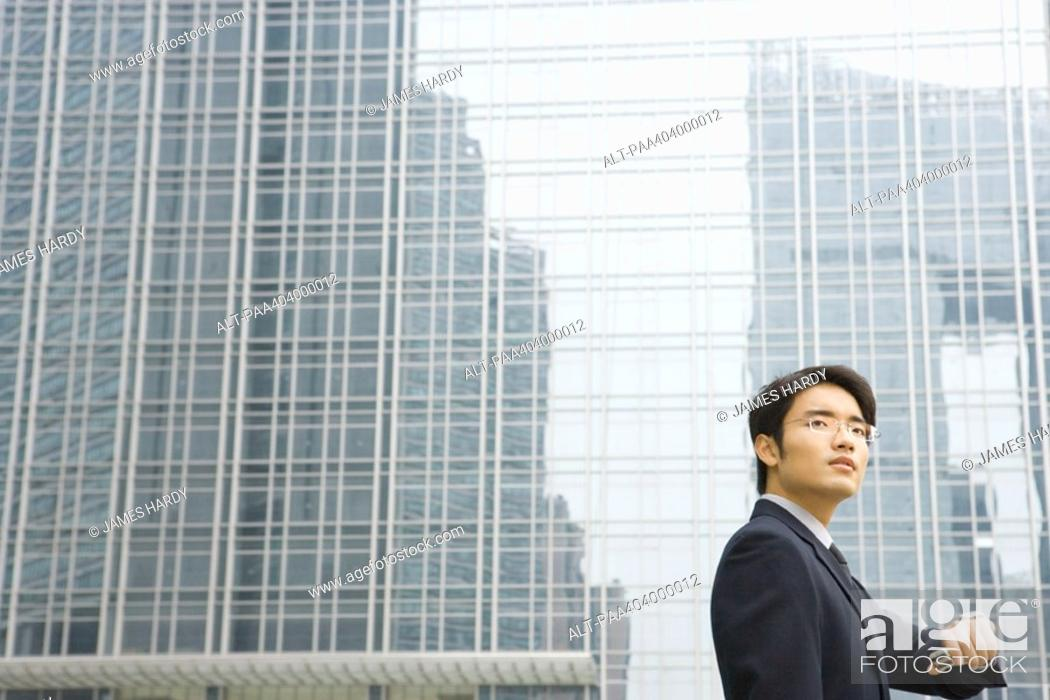 Stock Photo: Young businessman holding up wrist to check time, looking away, office building in background.