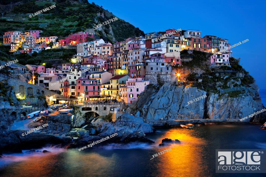 Stock Photo: Manarola view at dusk across harbor with light reflection on water.