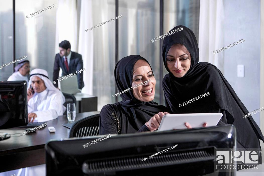 Stock Photo: Middle Eastern businesswomen in office looking at digital tablet.