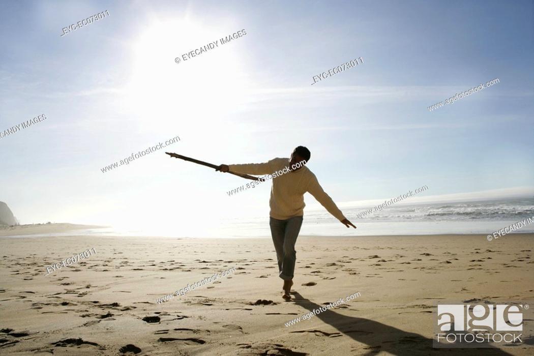 Stock Photo: Man walking on beach in winter.