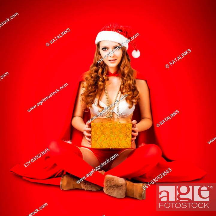 f898f95150ec0 Stock Photo - Sexy christmas woman wearing bikini and red santa claus hat  holding gift boxes on red background in studio