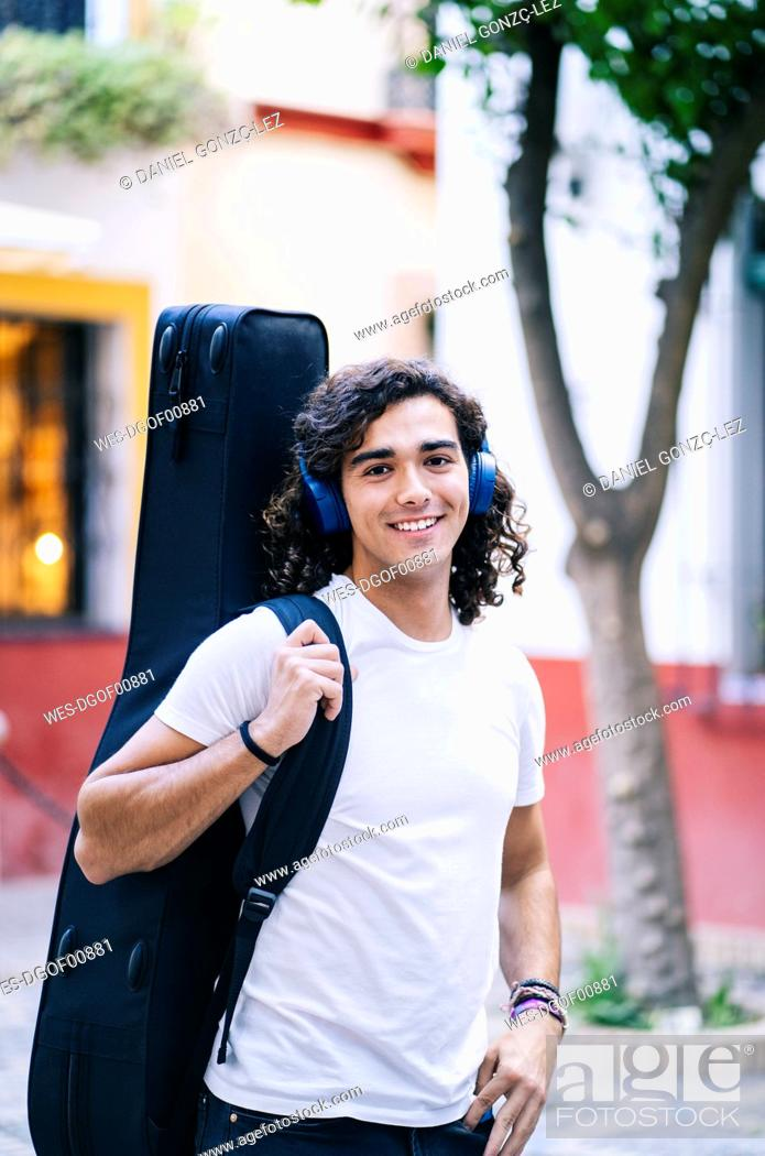 Stock Photo: Portrait of confident young man carrying guitar in bag while standing on street, Santa Cruz, Seville, Spain.