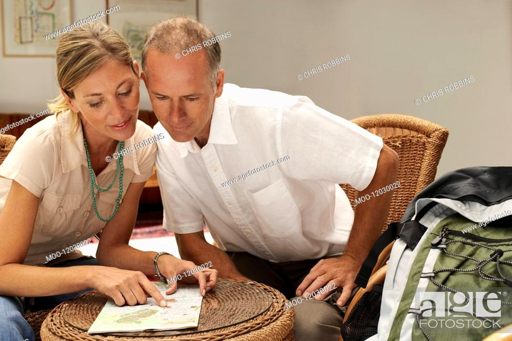 Stock Photo: Tourist Couple in Cafe looking at map front view.
