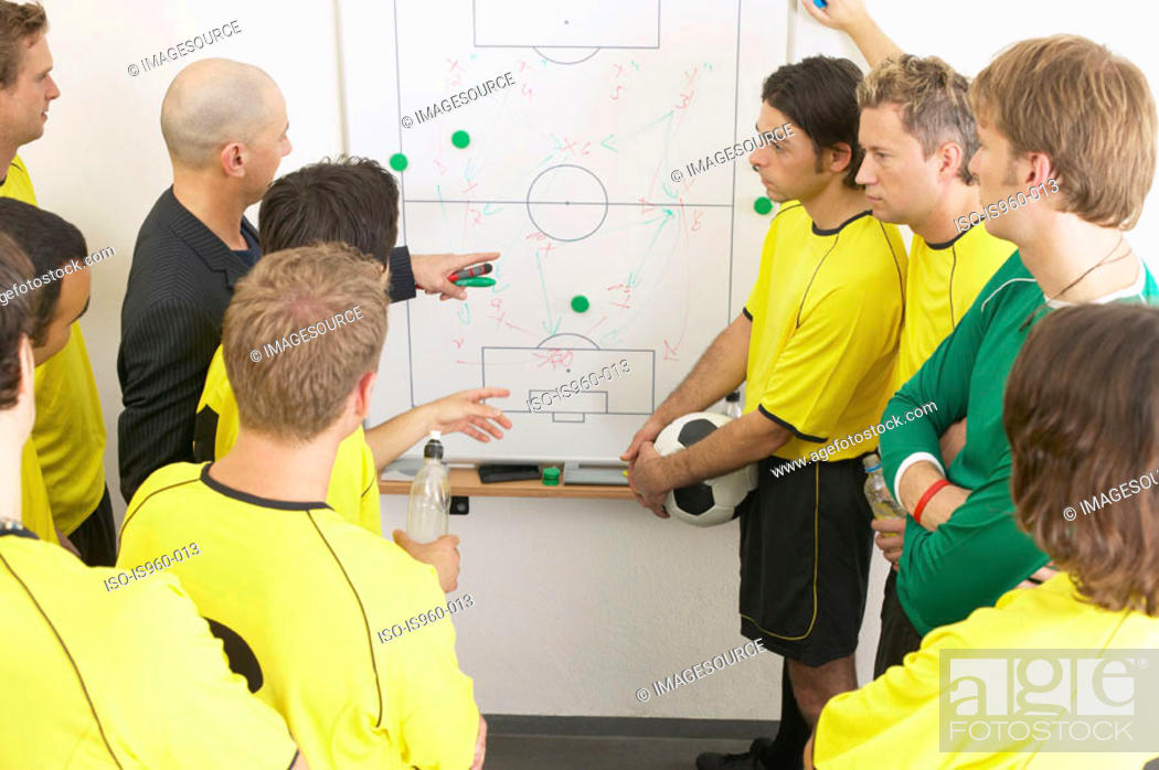 Stock Photo: Coach discussing strategy with soccer team.