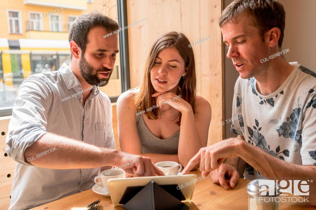 Photo de stock: Group of entrepreneurs meeting with coffee and digital tablet.