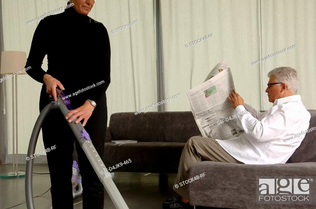 Stock Photo: Woman is vacuum-cleaning while her husband is reading newspaper.