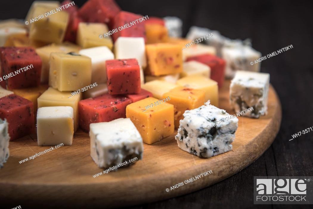 Imagen: many kinds of cheeses on wooden end of a tree.