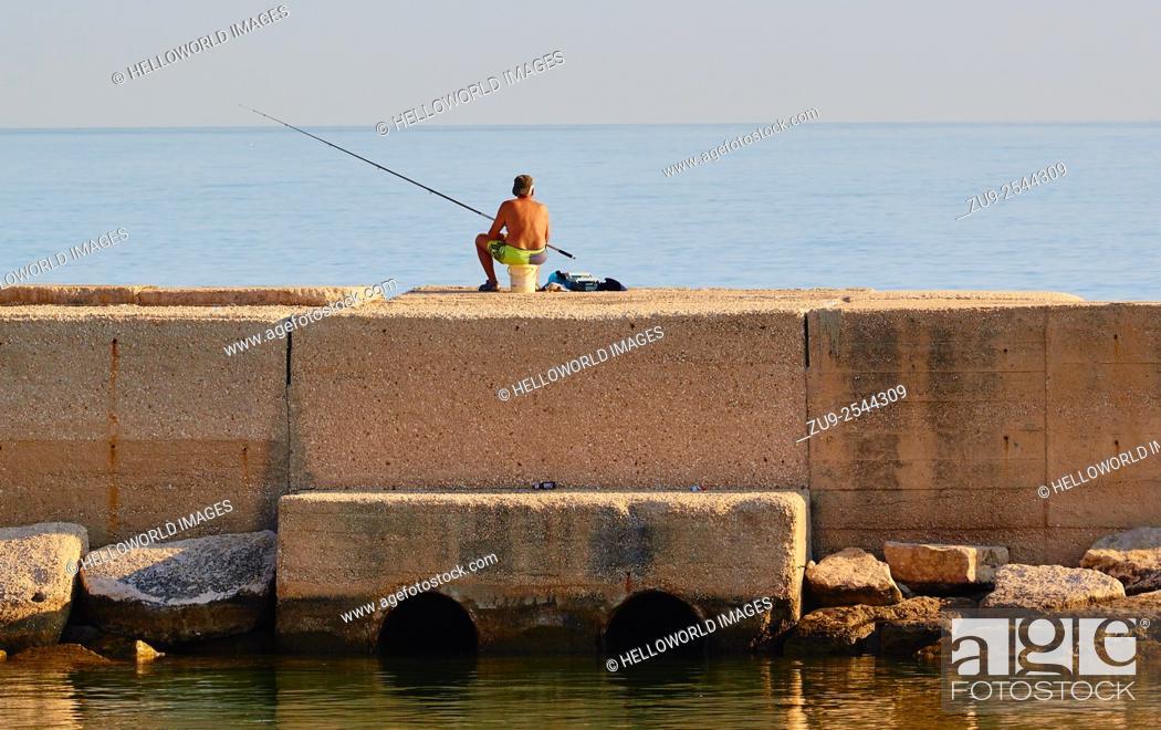 Stock Photo: Man fishing from pier, Molfetta, Puglia, Italy, Europe.