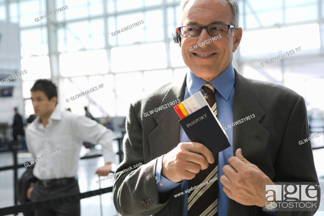 Stock Photo: Close-up of a businessman putting a passport with an airplane ticket in his coat's pocket.