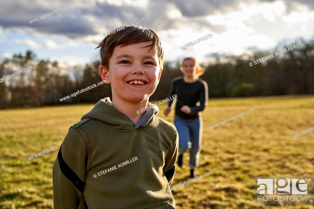Stock Photo: Portrait of happy boy with sister on a meadow.