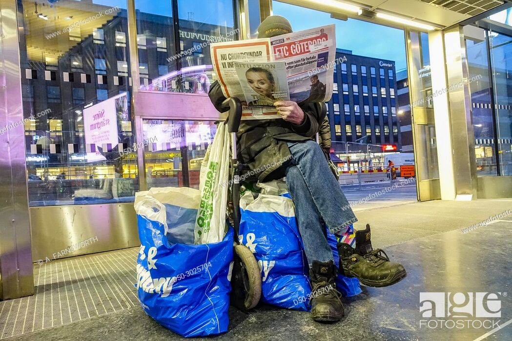 Homeless man sells magazine to support himself  In entry way to the