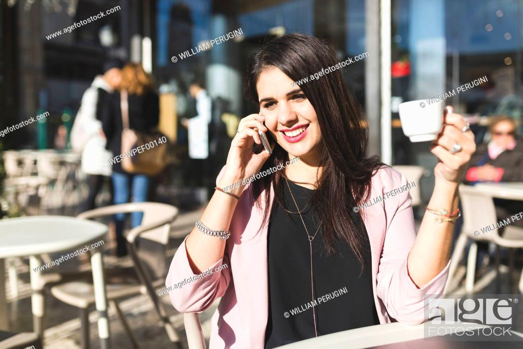 Stock Photo: Smiling young businesswoman on cell phone at an outdoor cafe.