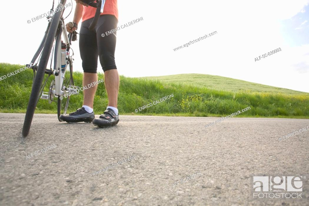 Stock Photo: Cyclist with bike, low section.