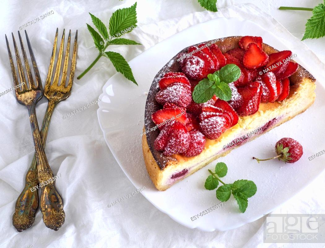 Stock Photo: Cheesecake of cottage cheese and fresh strawberries on a white ceramic plate, next to two forks, top view.