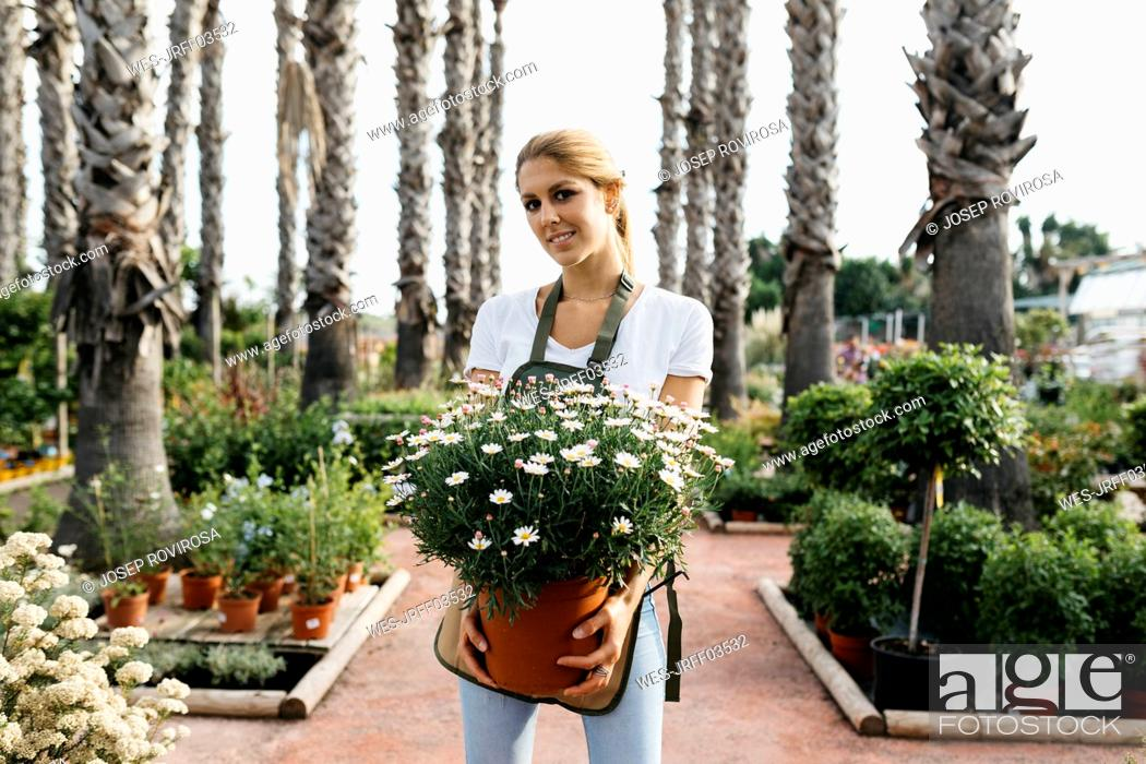 Imagen: Portrait of a smiling female worker in a garden center holding a daisy plant.