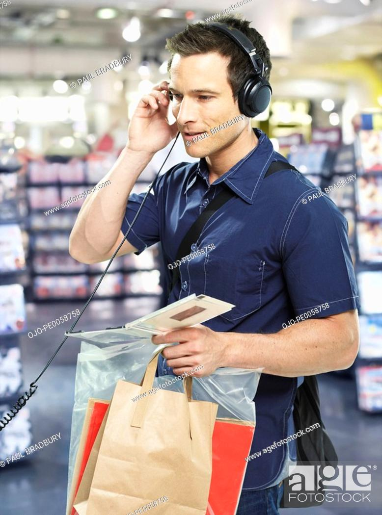 Stock Photo: Man wearing headphones with shopping bags in store.