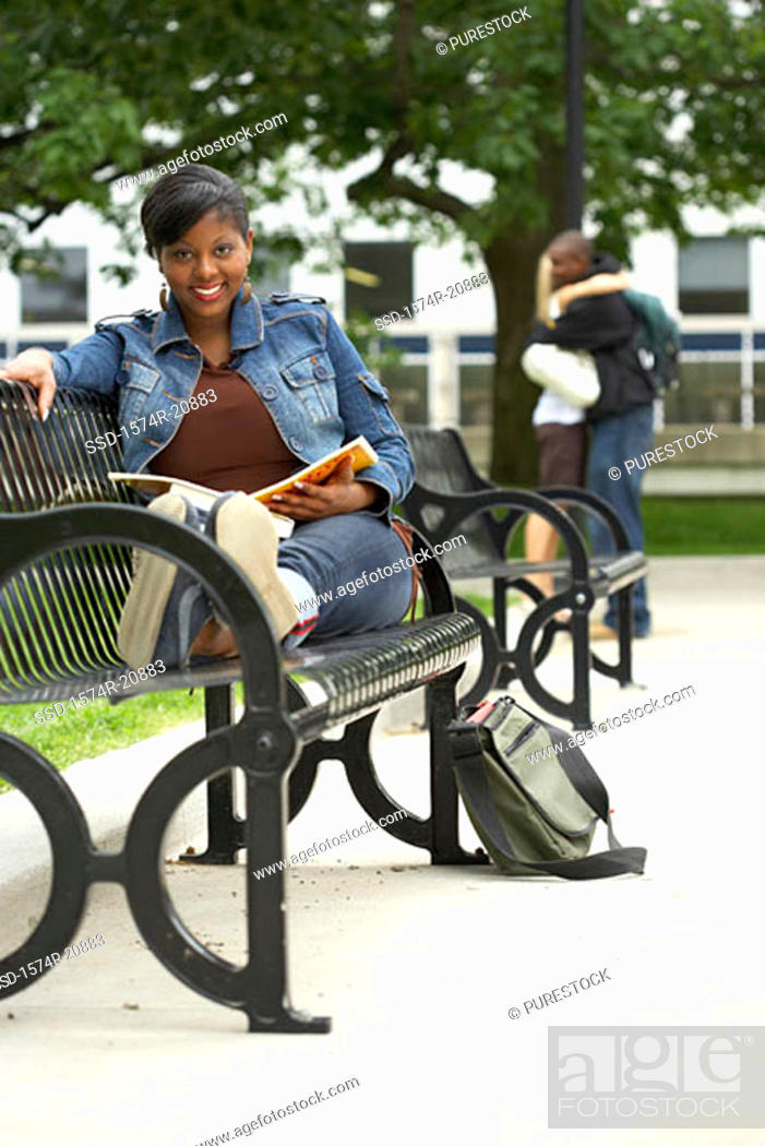 Stock Photo: Portrait of a college student sitting on a bench and smiling.