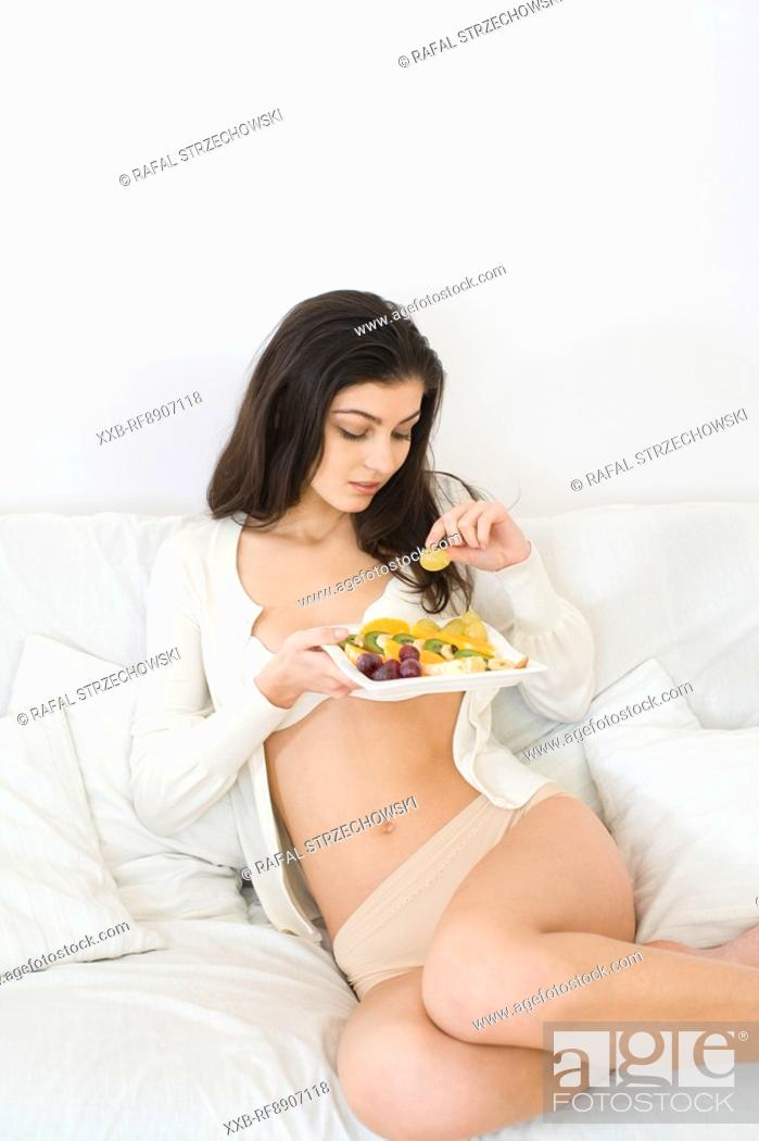 Stock Photo: young woman eating fruit salad.