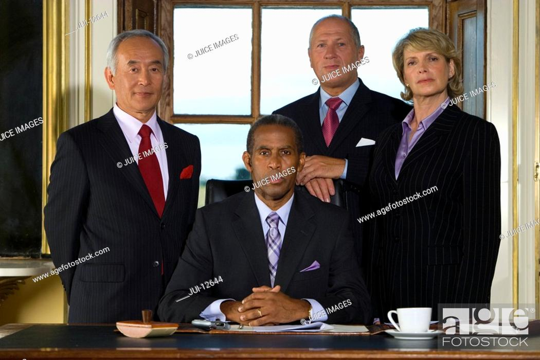 Stock Photo: Colleagues standing behind mature businessman at desk with paperwork, portrait.