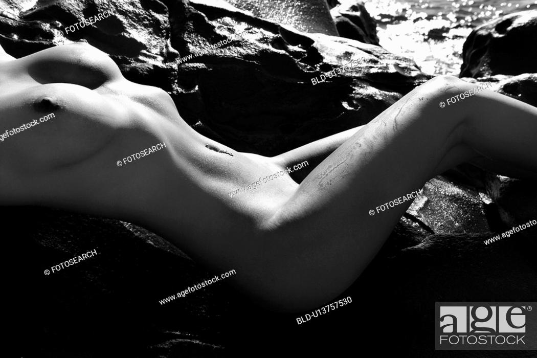 Stock Photo: Close up of sexy young adult woman sunbathing nude on rocks.