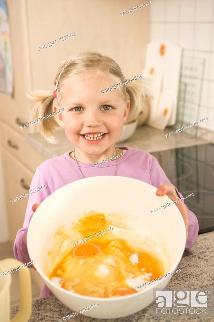 Stock Photo: Girl holding bowl of egg yolk and flour, smiling, portrait.