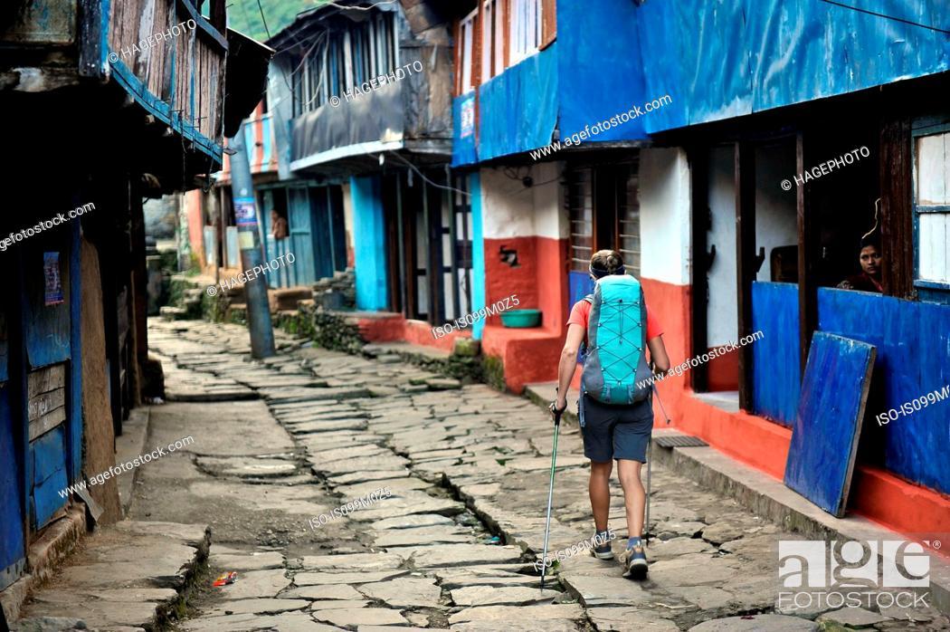 Photo de stock: Woman treks through a small village, Bhulbhule, Nepal.