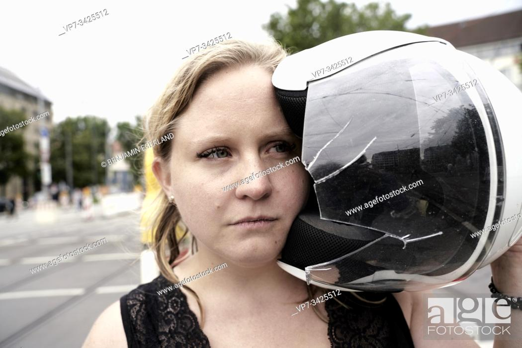Imagen: Woman holding motorcycle helmet with a shattered visor, Munich, Germany.