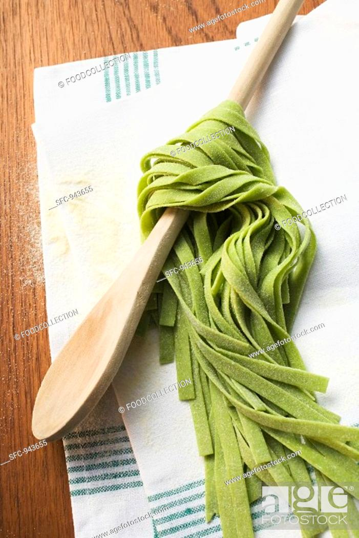 Stock Photo: Green ribbon pasta wrapped around a wooden spoon.