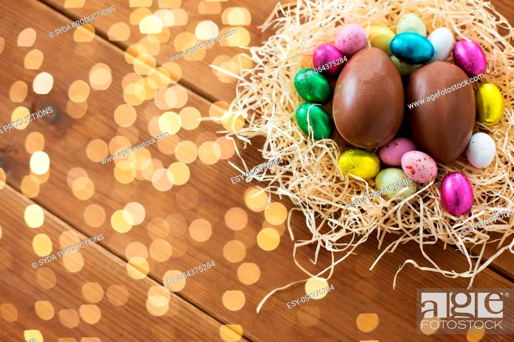 Stock Photo: chocolate eggs and candies in straw nest.