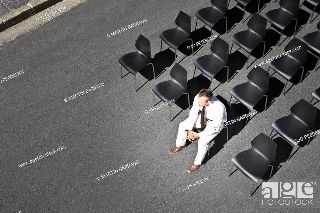 Stock Photo: Businessman sitting on office chair in roadway.