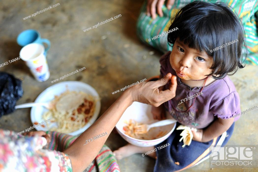 Stock Photo: A maya indigenous girl is fed lunch provided by local NPO in Aqua Escondida, Solola, Guatemala.