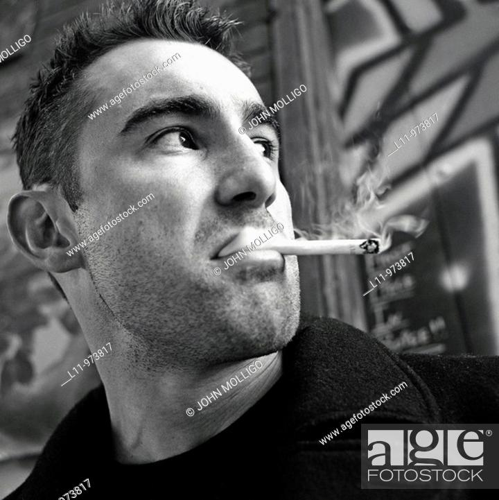Stock Photo: Close-up of man in alley, smoking a cigarette.