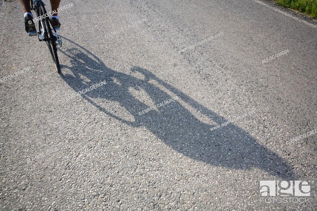 Stock Photo: Shadow of a bicyclist casting on road.