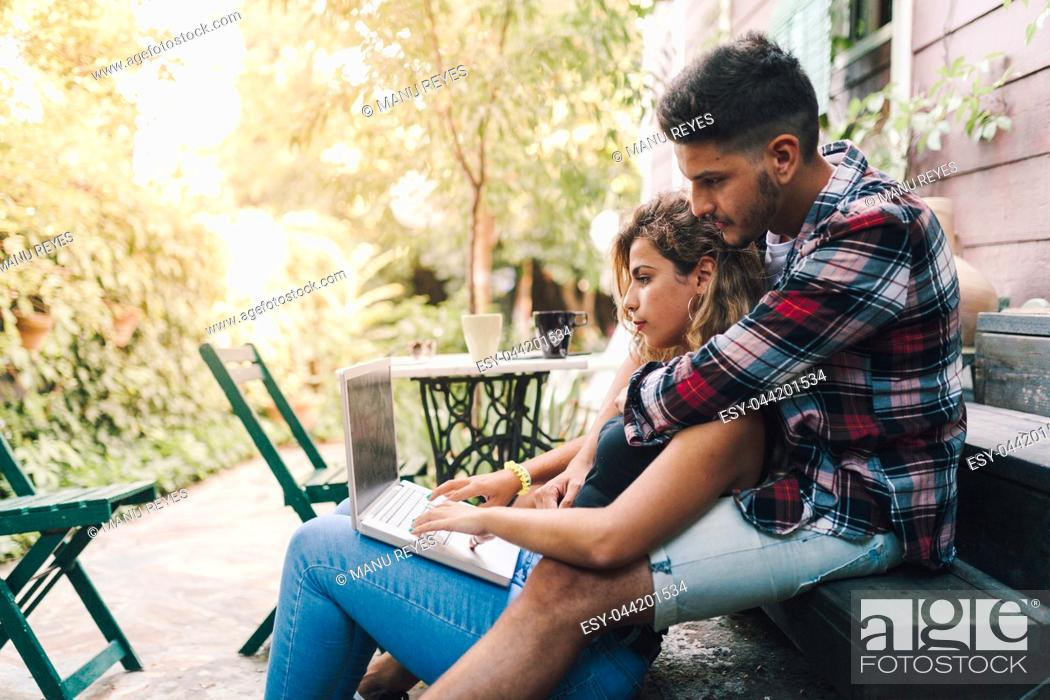 Photo de stock: Young couple sitting embraced in the steps of their wooden house with a laptop.