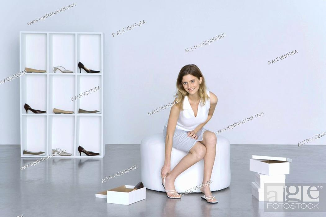Stock Photo: Woman trying on shoes, smiling at camera.