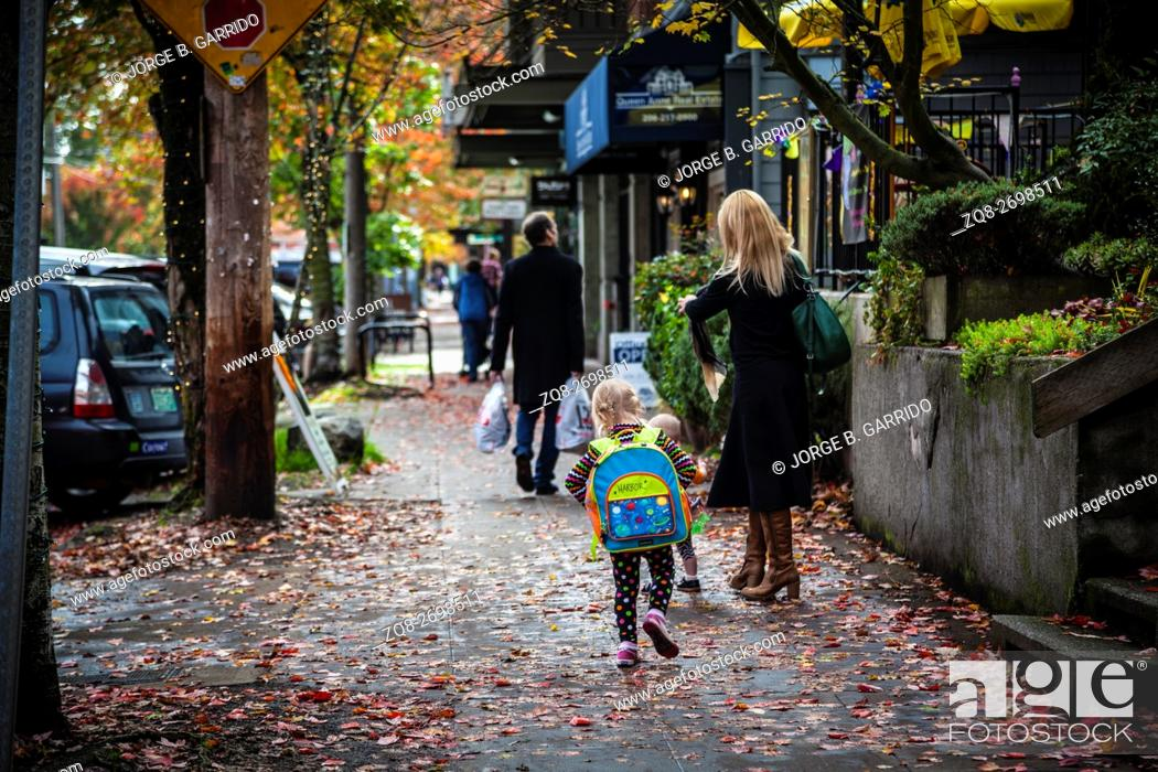 Stock Photo: Rear view of schoolgirl walking with mother on pavement, Seattle, Washington state.