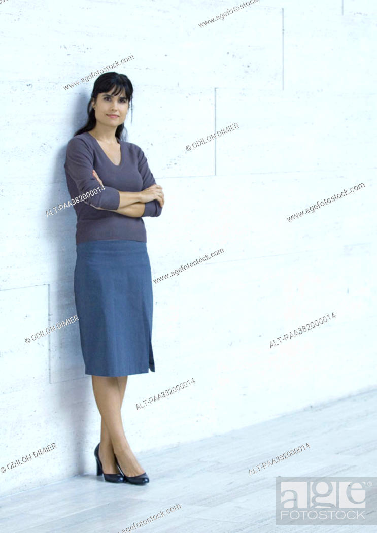 Stock Photo: Businesswoman standing, leaning against wall, full length.