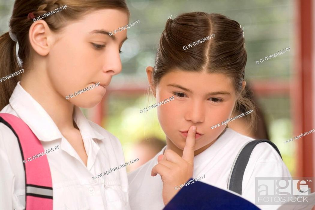 Stock Photo: Close-up of two schoolgirls looking at a textbook.