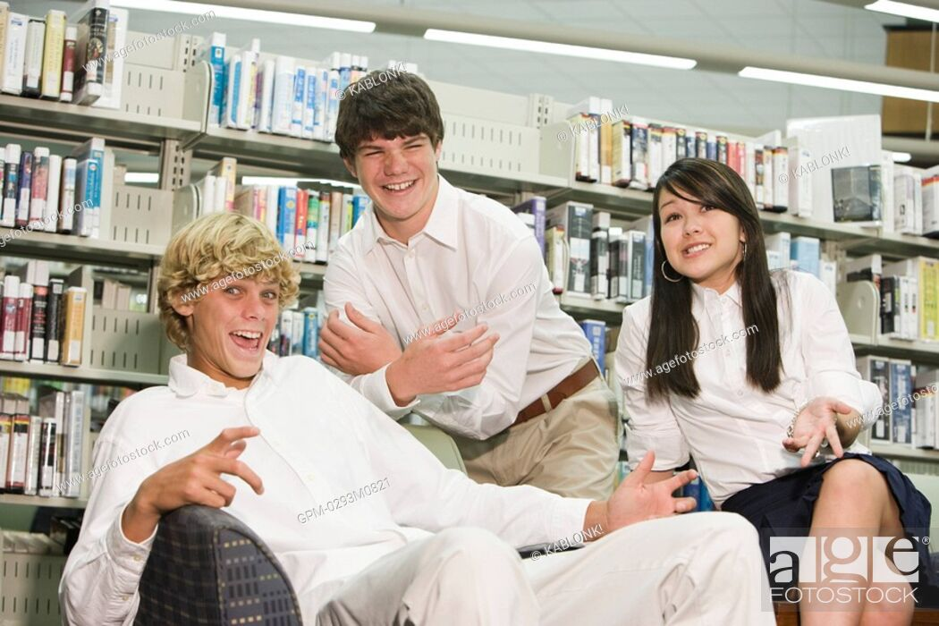 Imagen: Portrait of three high school students messing about in library.