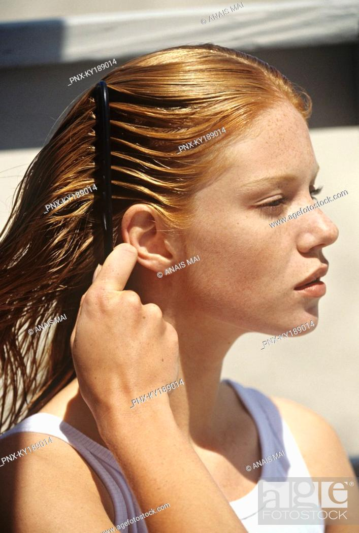 Stock Photo: Young woman combing her hair, outdoors.