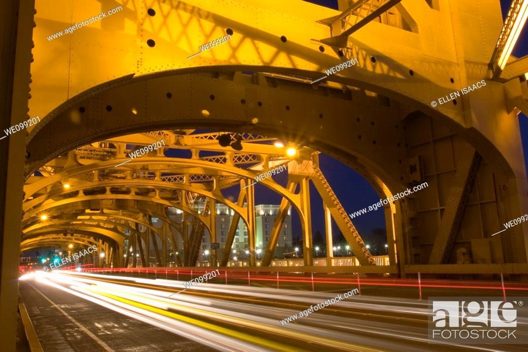 Stock Photo: Lights from cars traveling across the gold steel structure of Tower Bridge at night in Sacramento, California  The bridge is a vertical lift bridge and it spans.