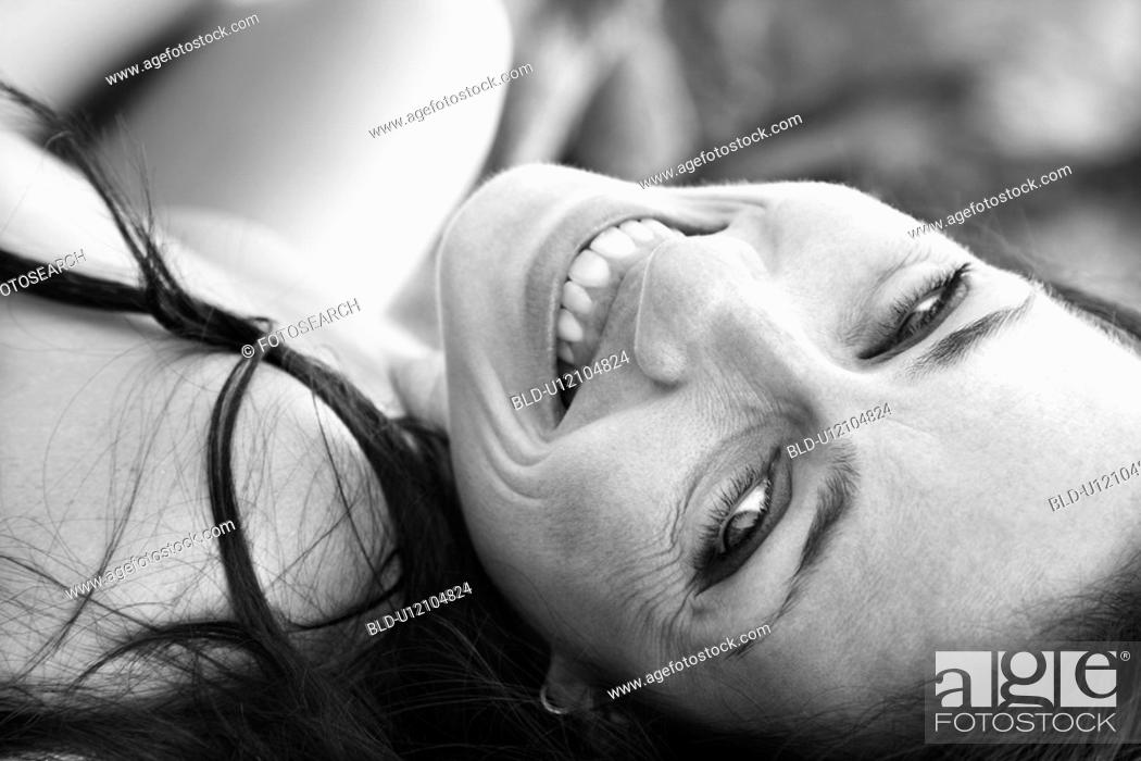 Stock Photo: Woman laying on back smiling and looking at viewer.