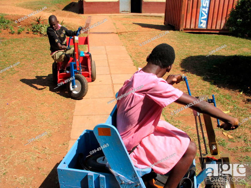 Stock Photo: A young boy and girl use special carts to exercise their upper bodies during a physiotherapy session at the Kamapala School for the Physically Handicapped.