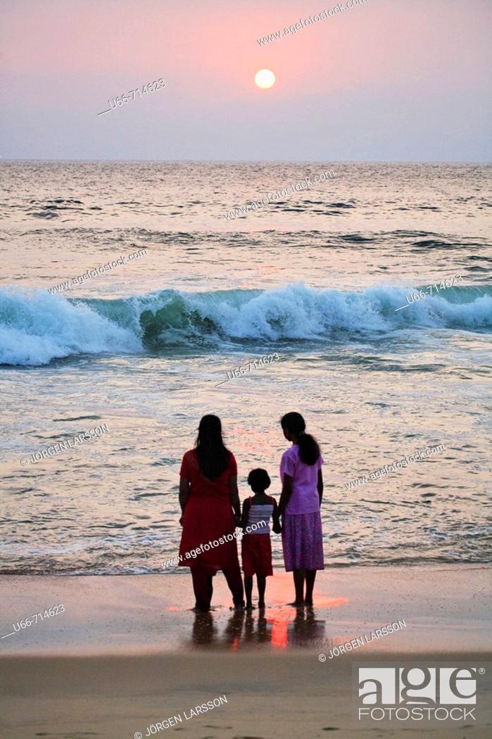 Stock Photo: Women and child watching sunset at Lighthouse beach, Kerala, India.