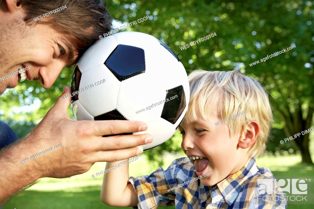 Stock Photo: Germany, Cologne, Father and son playing with soccer ball.