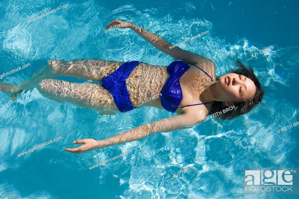 Stock Photo: A young Japanese woman swimming in a pool.