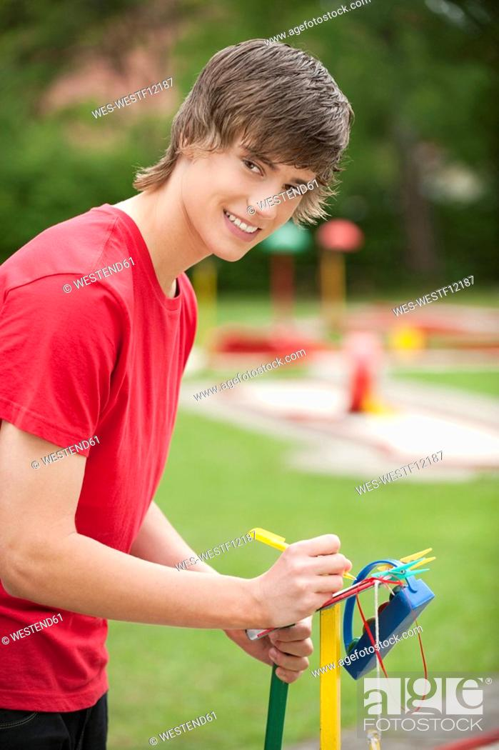 Stock Photo: Germany, Bavaria, Young man writing on score card, smiling, portrait.