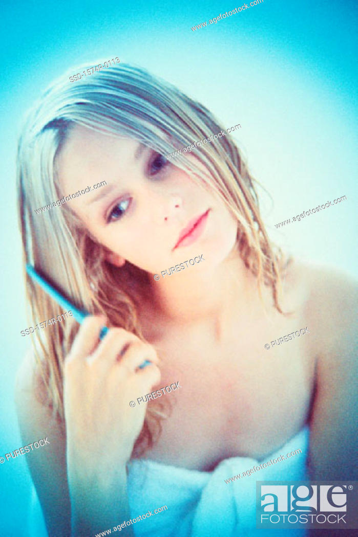 Stock Photo: Young woman combing her hair.