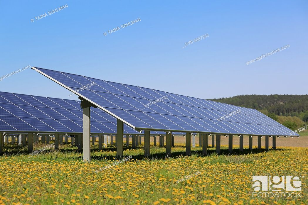 Stock Photo: Solar panels on an open green field with yellow flowers and blue sky in the spring. Salo, Finland.