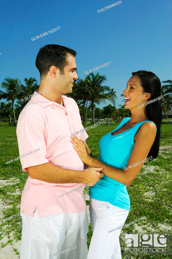 Stock Photo: Young couple looking at each other and smiling.